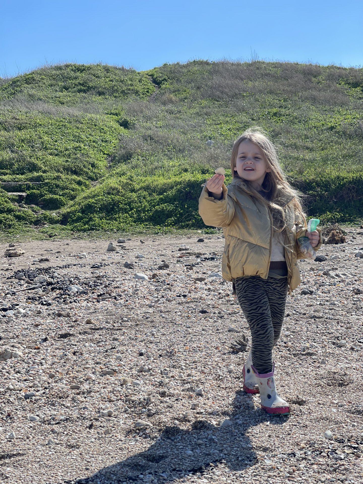 ילדה אוספת צדפים חוף שקמונה חיפה