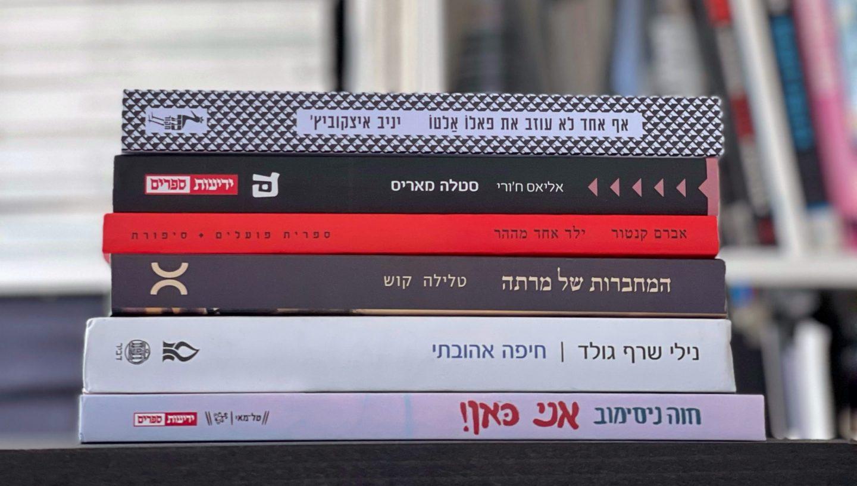 ספרים ישראלים על חיפה מונחים בערימת ספרים בספריה בבית